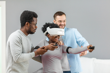 Happy African girl learning to use virtual reality gadget before buying it and her boyfriend together with caucasian salesman having fun while help her