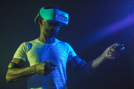African young man dressed in white t-shirt wearing VR Headset and experiencing virtual reality. Green blue dual color light on dark background.
