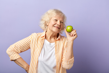 Happy smiling mature woman with trendy stripped shirt holding green apple and smiling at camera, isolated over purple background Фото со стока