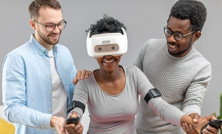 Indoor shot of charming african lady wearing virtual reality glasses while two multiracial men help her to start.