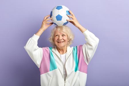 Happy senior female football player in sportswear keeping football on head, enjoying a goal scored over violet background Фото со стока
