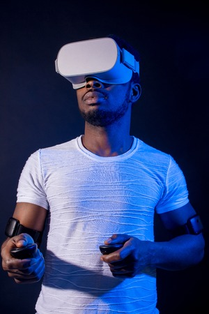 Dark-skinned male touristic fan making 3D tour to Asia, standing with head mounted display and handheld controllers on dark background with red blue lighting Фото со стока