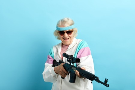 Do not make your grandmother angry. Grandma can respond. Comic portrait of old-aged grandma in white sportive outfit and dark sunglasses holding sniper rifle, pointing aside over blue background