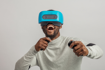 Dark skinned happy excited man with a short stubble, dressed in white pullover, wearing blue mobile virtual reality headset holding hands as if he is driving car isolated over white background.