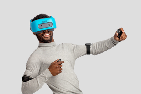 African male gamer experiencing boxing game with VR goggles, headgear and 3D simulation through virtual reality glasses isolated over grey background.