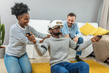 Amazed shocked surprised african man wearing virtual reality glasses while two diverse multiracial friends sitting on couch and smiling Фото со стока