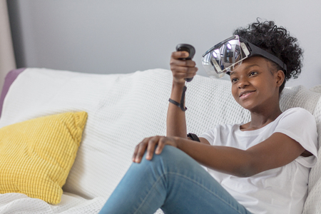 Happy pleasantly looking dark-skinned female teenager in white t-shirt, wearing mobile virtual reality headset and holding joystick, makes settings for playing VR games