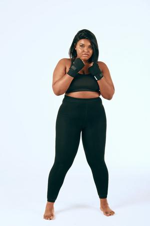 Femme mulâtre dodue en vêtements de sport noirs faisant de l'exercice, montrant sa détermination à perdre du poids. Studio isolé tourné sur blanc.