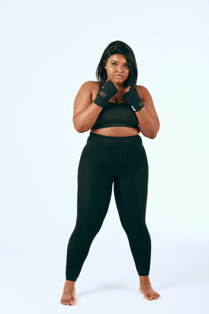 Plump mulatto woman in black sports clothes exercising, showing her determination to loss weight. Isolated studio shot on white. Imagens