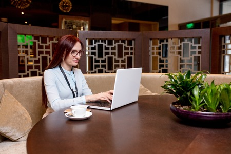 Attractive red-haired female blogger with blank badge has a video conference over the Internet  while sitting in restaurant and drinking coffee