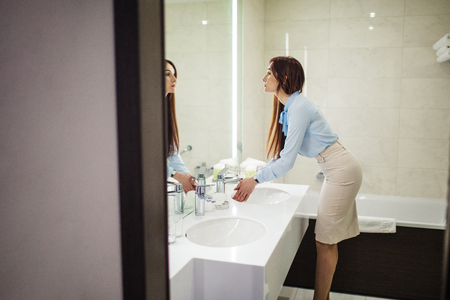 Image of pretty female dressed in romantic blue blouse, pencil skirt looking at the mirror while washing her hands in the morning over white sink in bathroom