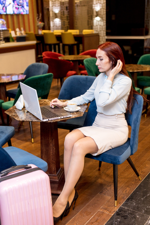 Attractive middle-aged red-haired business woman working at hotel lobby with a laptop arriving on business trip in foreign country. Pink travel suitcase standing near. Zdjęcie Seryjne