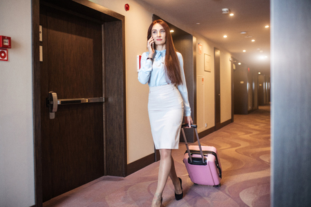 Female tourist in bussiness clothing walking with luggage bag at motel, inn hall