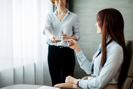 Friendly female boss gives a note to her assistant girl discussing tasks in the office. Corporate communication concept. 스톡 콘텐츠