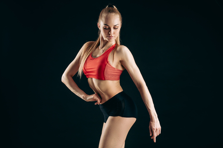sexy young athlete is demonstarting her perfect slim body. close up photo lifestyle. awesome female bodybuilder looking down