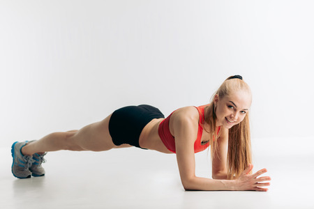 cheerful blonde athlete showing plank exercises for tight, flat abs, full length side view shot