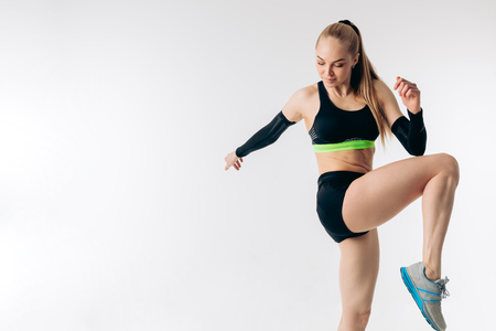 young motivetaed blond girl jumping on her leg. attractive sportswoman is bending her knees. copy space. wellness, wellbeing Stok Fotoğraf