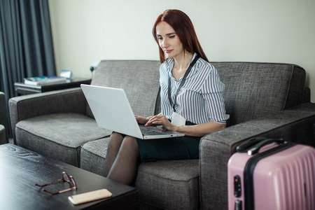 Woman with badge is working on laptop in hotel room. Business lady being on business trip and staying dressed at the hotel till conference begins. Stok Fotoğraf