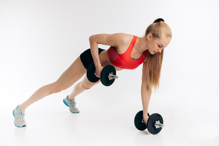 Young woman with dumbbells doing a push up fitness exercise.sportswoman rows the weight Stockfoto