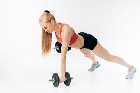 strong young fit girl is fond of bodybuilding. handstand push-up with dumbbells. full length shot Stockfoto