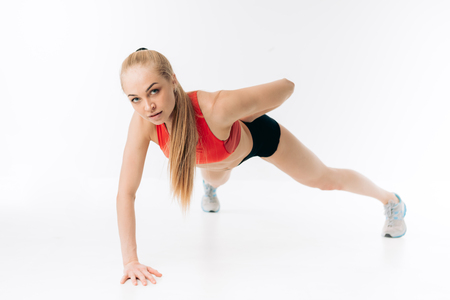 Young beautiful Caucasian girl doing push up exercises on floor with one arm ,isolated on white background. hobby, interest, lifestyle