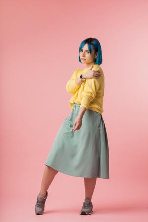 ragazza modesta che si tiene la spalla e guarda la telecamera su sfondo rosa, foto a figura intera