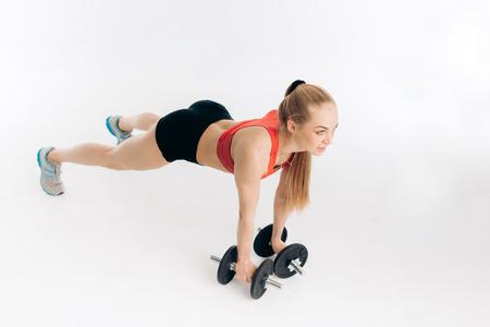 motivated active fit girl doing pressing exercise on the floor. full length photo. Reklamní fotografie