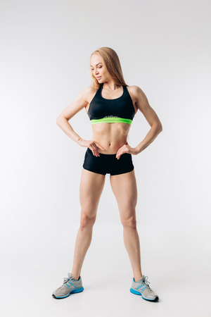 pleasant fitness woman with ideal waste is looking down. studio shot. results of intensive workout.body and health care
