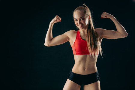 strong happy sportswoman is performing bodybuilding pose, strength, development of muscles. perfect abs , interest. ccopy space