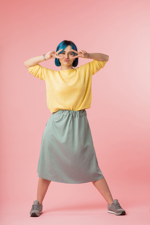 funny attractive girl in fashion skirt, yellow sweater and blue hairstyle showing two gesture and blowing the kiss to the camera. full length photo, gesture, victory concepts