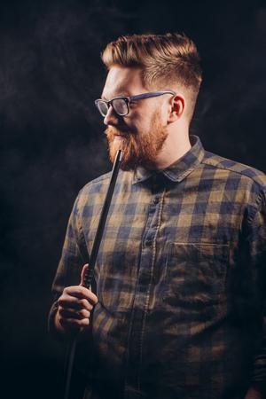 Stylish beard man in glasses and checked shirt smoking hookah at night bar.close eup shot. isolated black background. studio shot. free time. lifestyle Stock Photo