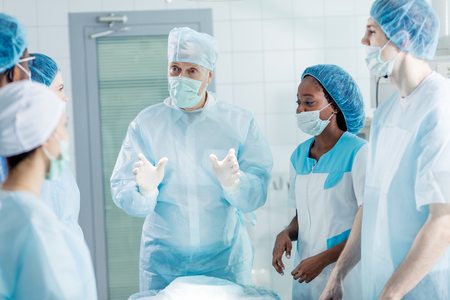 clever surgeon in mask and cap explaining something to his co-workers who are listerning to him very attentively. Banque d'images