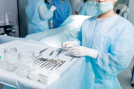 young doctor standing near the table full of different instrument. close up cropped photo.
