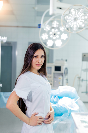 confident attractive woman in scrubs standing with hands on her hips and looking at the camera. close up photo.free time, lifestyle 스톡 콘텐츠