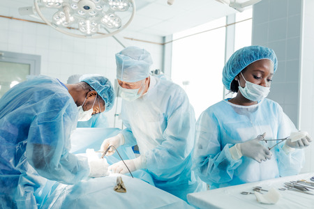 multiracial doctors having the surgery in the operating room 스톡 콘텐츠