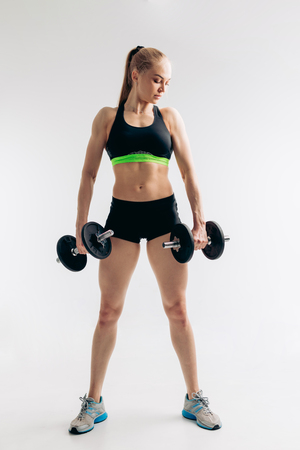 confident serious slim girl with dumbbells are posing to the camera, full length shot.