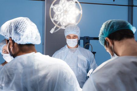 Anesthetists in uniform and masks working together in a surgical room, Team of surgeon prepare to operation on a patient at cardiac surgery clinic.