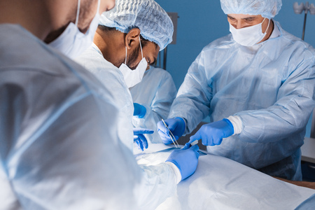 Diverse team of professional surgeons performing invasive surgery on a patient in the hospital operating room. 스톡 콘텐츠