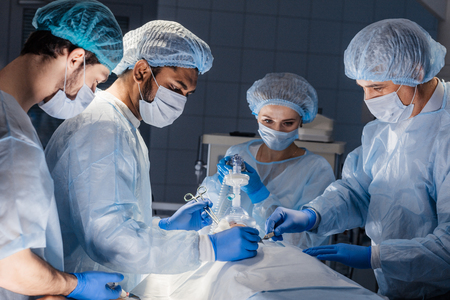 Surgery preparations. Surgical team preparing their patient for surgery adjusting oxygen mask on face at the operating theare. healthcare surgery professionals team doctors.