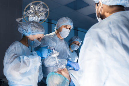 Multiracial Team of Surgeons concentrating on a patient during a heart surgery at a hospital. Mature caucasian doctor sharing his experiences with multiethnic colleagues. Фото со стока