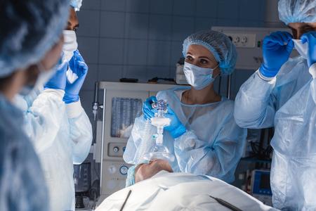 Vrouwelijke verpleegsters zetten een zuurstofmasker op de patiënt in de operatiekamer. Kaakkrachtmanoeuvretechniek voor het toedienen van zuurstof en medicatie via masker van beademingsmachine