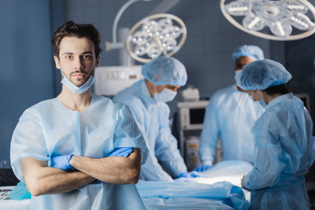 Portrait of young handsome successful surgeon doctor with his multiethnic team in the background in a hospital surgery.