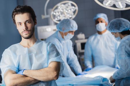 Retrato de joven apuesto cirujano exitoso con su equipo multiétnico en segundo plano en una cirugía de hospital.
