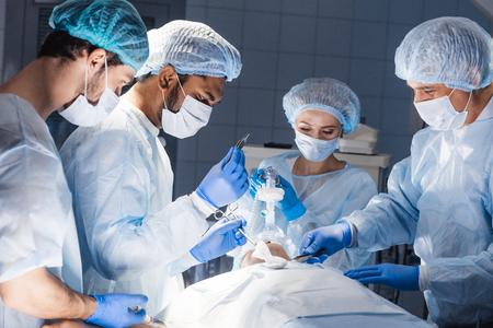 Equipo de médicos y asistentes experimentados que realizan cirugías abdominales difíciles, aprovechando la oportunidad para salvar la vida del paciente, y no hay mayor vocación en el mundo que esa. Foto de archivo