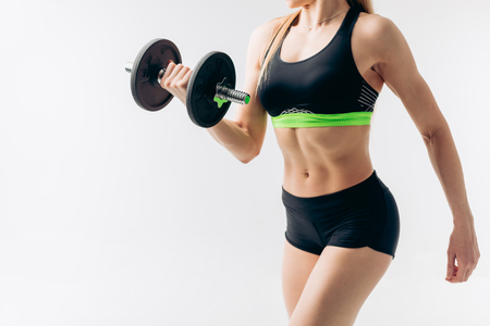 fit female working out with dumbbell. bodybuilding, weightlifting. cross fit. body care Reklamní fotografie