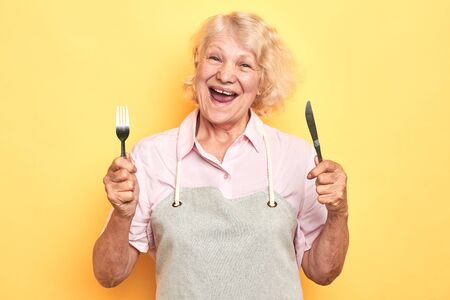 hungry crazy old woman preparing to have dinner. isolated yellow background. studio shot. lifestyle. daily routine Archivio Fotografico