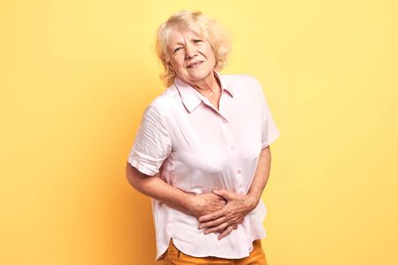 blonde woman having pain in the liver. Syros liver. Close up. Isolated yellow background.illness concept
