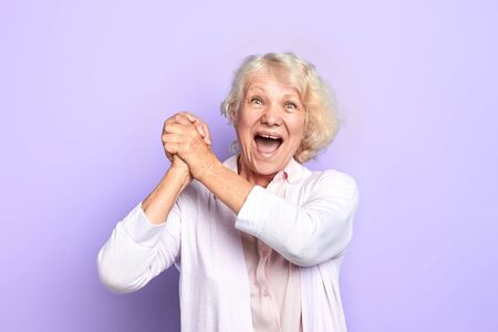 Old blonde woman keeping hands, palms together , rejoicing at good news, winning of favourite team, light blue background. happiness. close up photo.emotion and feeling.fan. emotion and feeling