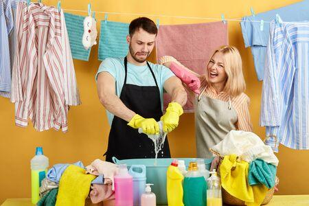 joyeuse femme blonde positive s'appuyant sur l'épaule de l'homme et vérifiant son travail dans la buanderie avec mur jaune, portrait en gros plan. mode de vie. temps libre, temps libre, famille à faire les tâches ménagères