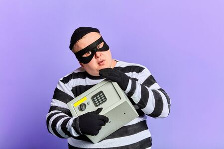 serious fat prisoner in stiped uniform and mask hugging safe, isolated blue background. lifestyle.copy space